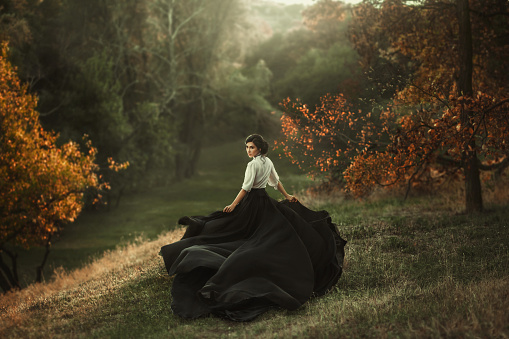 istock mysterious girl with dark hair and a long flying black vintage dress runs through the woods, a charming ambush, a great attractive witch turns into a crow, waving a train like bird wings 1141013985