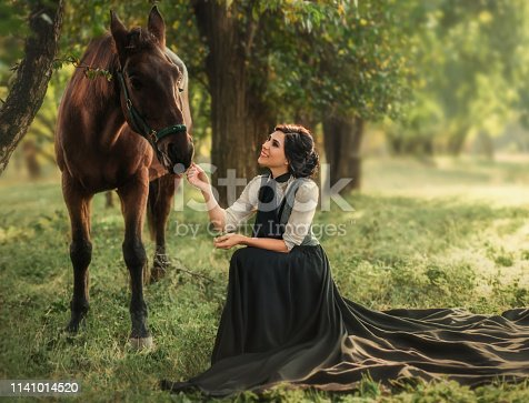 Gourmet lady in a vintage dress. Beautiful girl laughs looking at her horse. Artistic Photography