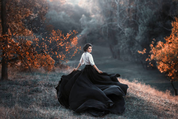 mysterious girl with dark hair and a long flying black vintage dress runs through the woods, a charming ambush, a great attractive witch turns into a crow, waving a train like bird wings A girl in a vintage dress is running and looking around. The train waving in the wind. Artistic Photography gothic style stock pictures, royalty-free photos & images