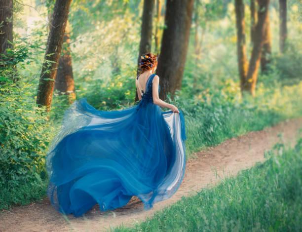 geheimnisvolles mädchen mit roten geflochtenen haaren läuft weg von königlichen urlaub, dame in langen eleganten blauen kleid mit fliegenden leichten zug wie blume, die magische verwandlung der schönen frau während des sonnenuntergangs - abendkleid lang blau stock-fotos und bilder