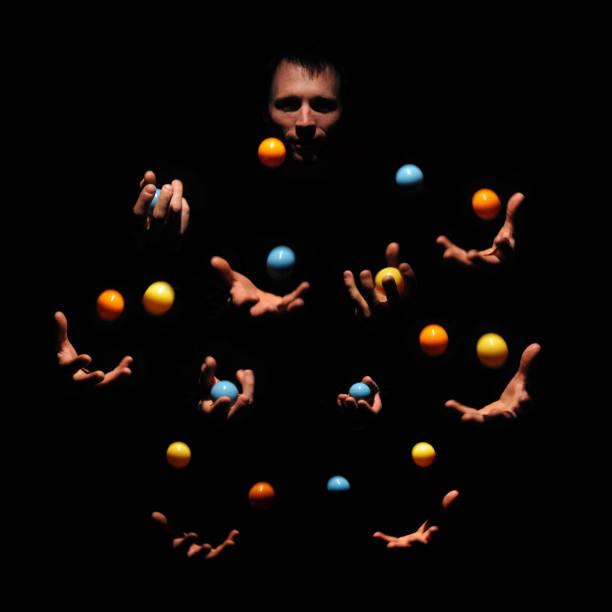 Mysterious juggling man in dark. Ten hands concept of success stock photo