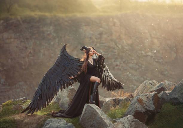 geheimnisvolle dame in schwarzem lichter-kleid mit langem zug, mädchen mit offenem bein in lederstiefeln, dunkler gehörnter engel vom himmel, todesboten mit großen flügeln auf kante mit geschlossenen augen in sonnenstrahlen - elfenkostüm damen stock-fotos und bilder