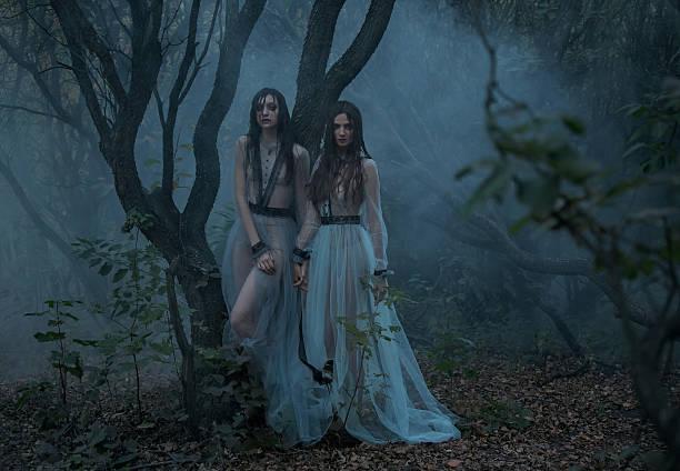mysterious lady with long black hair walk in spooky woods - anzieh nacht stock-fotos und bilder