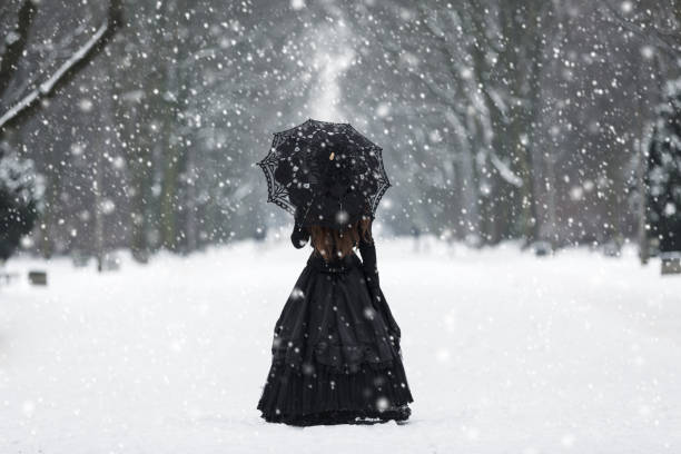 Mysterious lonely woman in Victorian dress departing into the distance stock photo