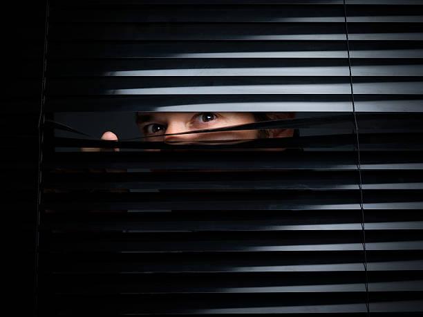 geheimnisvolle männliche treiben von eröffnung im jalousie - peeping tom stock-fotos und bilder