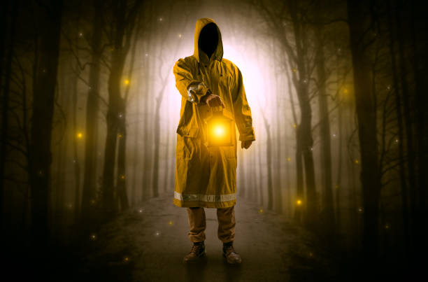 Mysterious man coming from a path in the forest with glowing lantern concept Man in raincoat coming from dark forest with glowing lantern in his hand concept bootes stock pictures, royalty-free photos & images