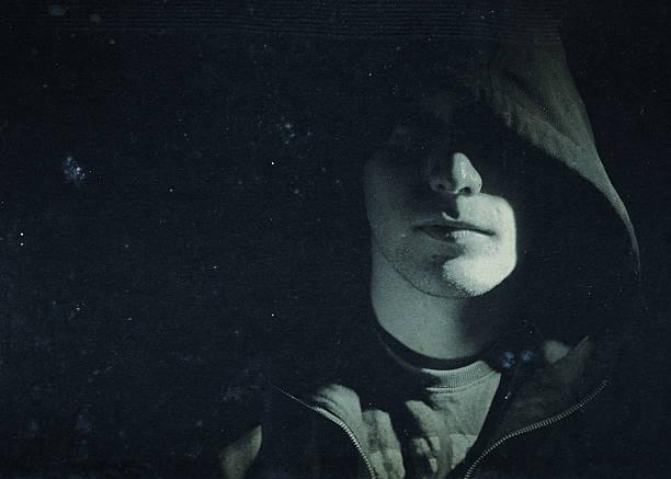 mysterious man hidden under a hooded shirt stock photo