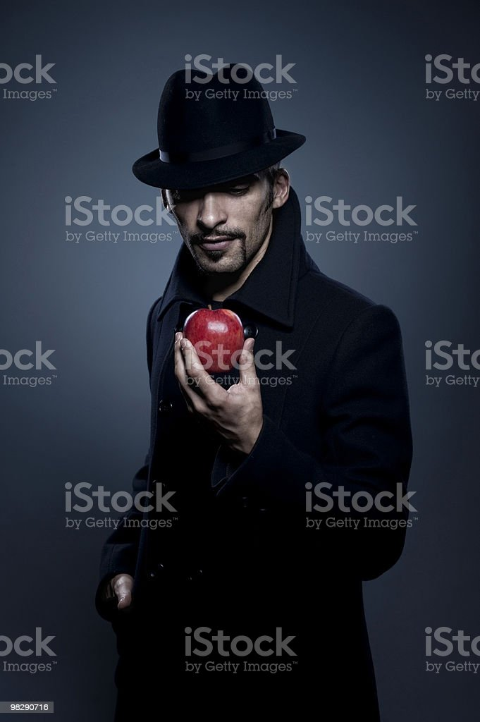 Mysterious man holding an apple royalty-free stock photo