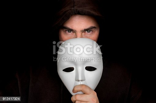 istock Mysterious man in black hiding his face behind white mask 912417324