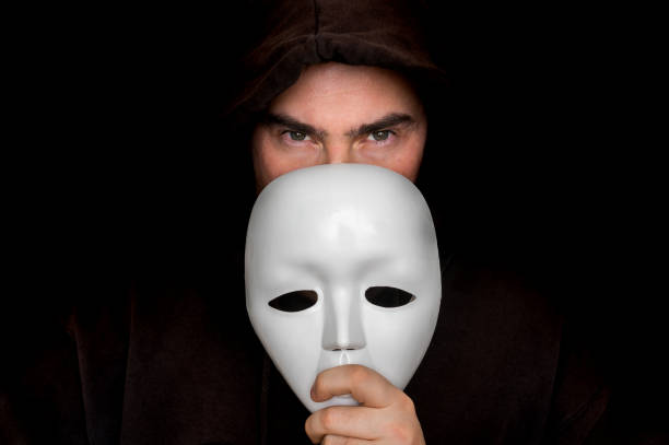 Mysterious man in black hiding his face behind white mask stock photo