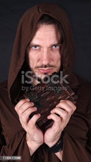 This is a mysterious man in hood with old book of ancient secret text.