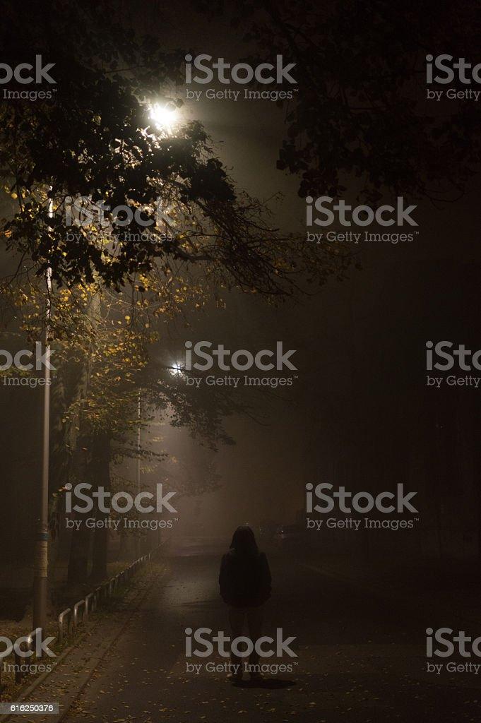 Mysterious man in the hood, alone on dark street stock photo