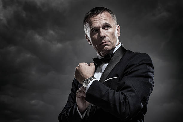 Mysterious Man in Tuxedo A handsome mature male secret agent, bodyguard, spy, or security staff dressed in an elegant tuxedo and bow tie as he adjusts his watch or cuff links on a stormy night with cloudy sky in the background. tuxedo stock pictures, royalty-free photos & images