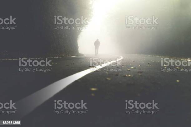 Photo of mysterious man walking in the mist