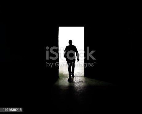 Mysterious man walking through door in between darkness and light