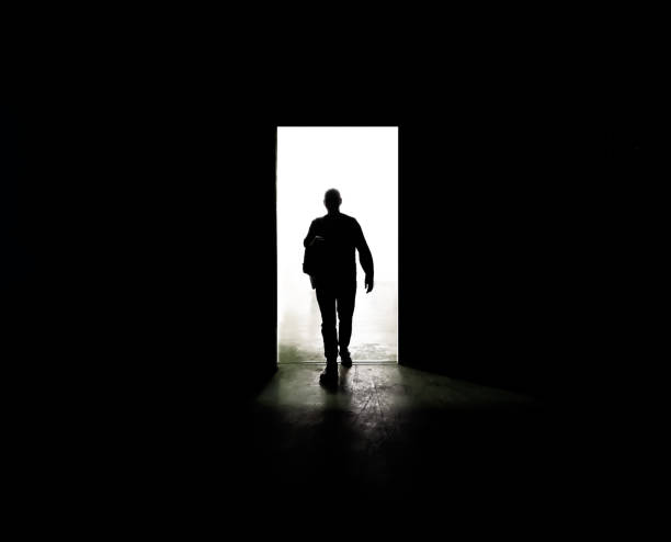 Mysterious man walking through door in between darkness and light stock photo
