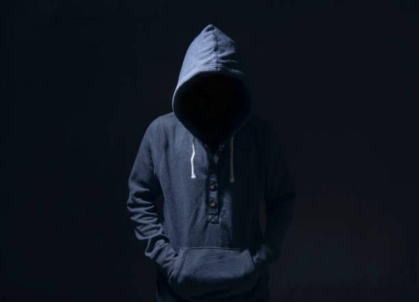Geheimnisvoller Mann mit Kapuze in der Silhouette auf schwarzem Hintergrund. ein Konzept von Verbrechen begangen. – Foto