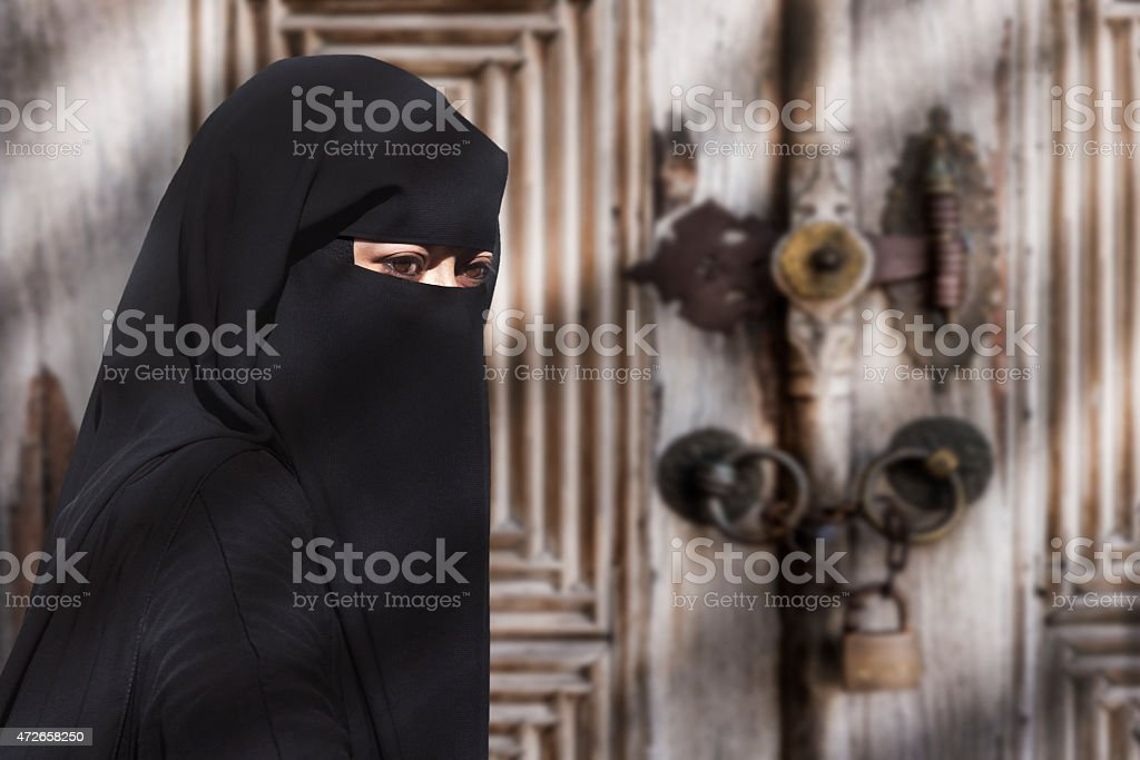 A mysterious Middle Eastern woman wearing a black Niqab stock photo