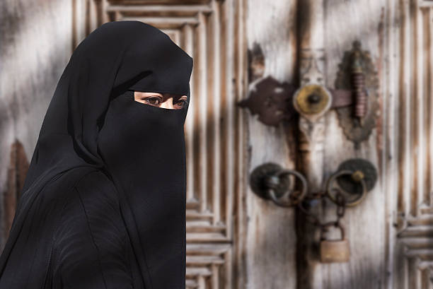 A mysterious Middle Eastern woman wearing a black Niqab Impossible to recognize this woman behind this complete attire religious veil stock pictures, royalty-free photos & images