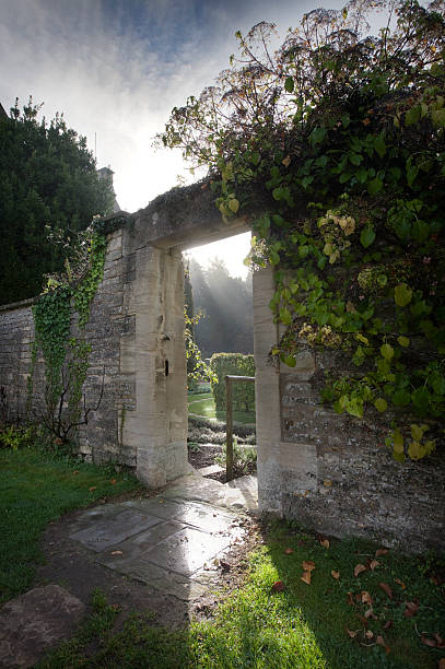 geheimnisvolle offener durchgang führt zu einer geheimen garten - steine für gartenmauer stock-fotos und bilder