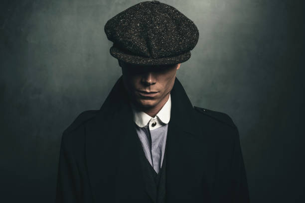 Mysterious portrait of retro 1920s english gangster with flat cap. stock photo