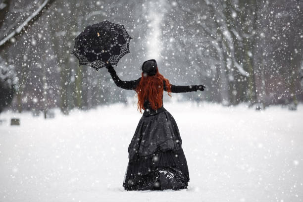 Mysterious red-haired woman in Victorian dress in the winter park stock photo