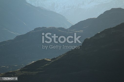 Four dark, stepped ridges with snowy mountains behind