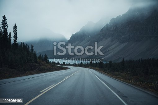 istock Mysterious road trip with rocky mountains in misty on gloomy at Banff national park 1226066493