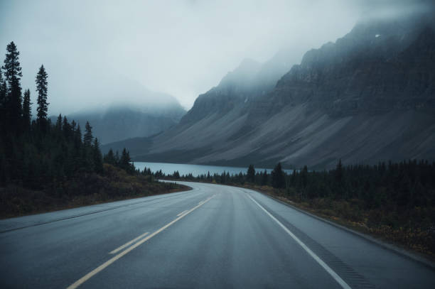 Mysterious road trip with rocky mountains in misty on gloomy at Banff national park stock photo