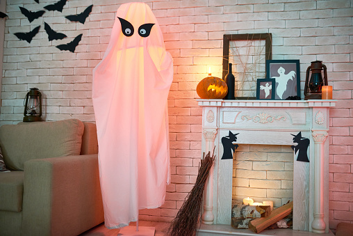 Common living room with sofa and fireplace decorated with Halloween toys and crafts such as lanterns, frames with ghosts, paper bats and withes, big ghost from fabric and broom