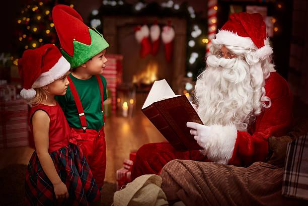 geheimnisvolle santa claus lesen ein buch mit kindern - nikolaus geschichte stock-fotos und bilder