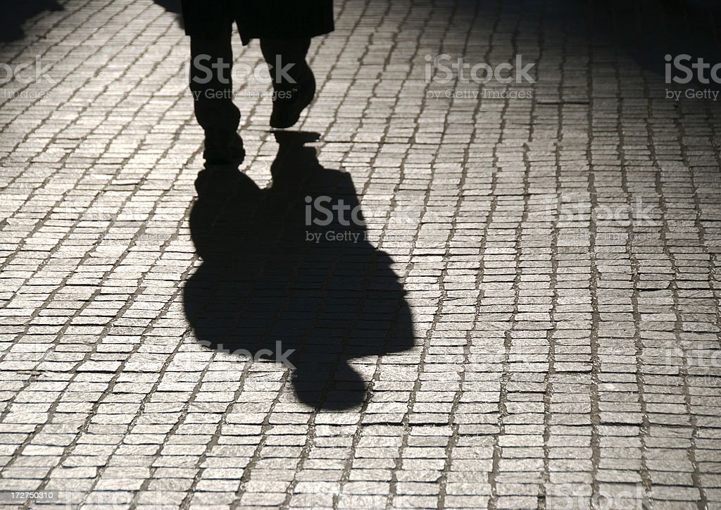 Mysterious Shadow Figure of Businessman Walking on Cobblestones royalty-free stock photo