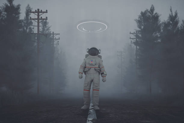 mysterious ufo and walking astronaut on the forest road at night - conspiracy стоковые фото и изображения