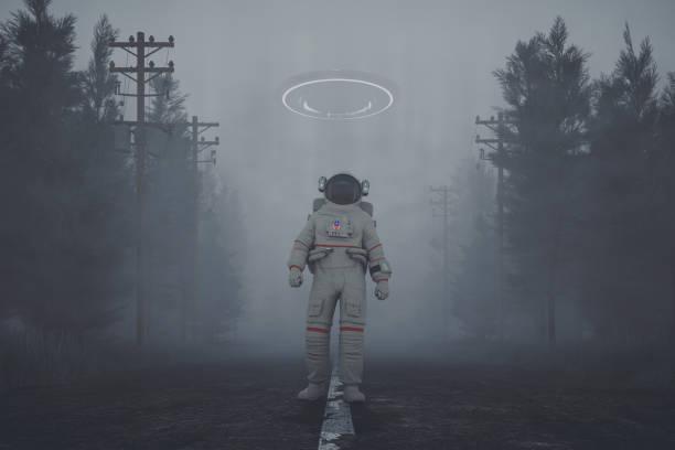 misterioso ovni y astronauta caminando en la carretera del bosque en la noche - conspiración fotografías e imágenes de stock
