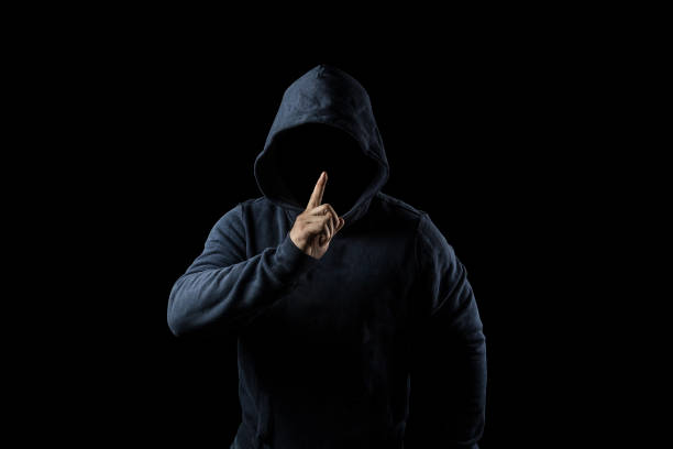 Mysterious, unknown person in the hood. Danger in darkness. anonymous or criminal concept Mysterious, unknown person in the hood. Danger in darkness. anonymous or criminal concept creepy stalker stock pictures, royalty-free photos & images