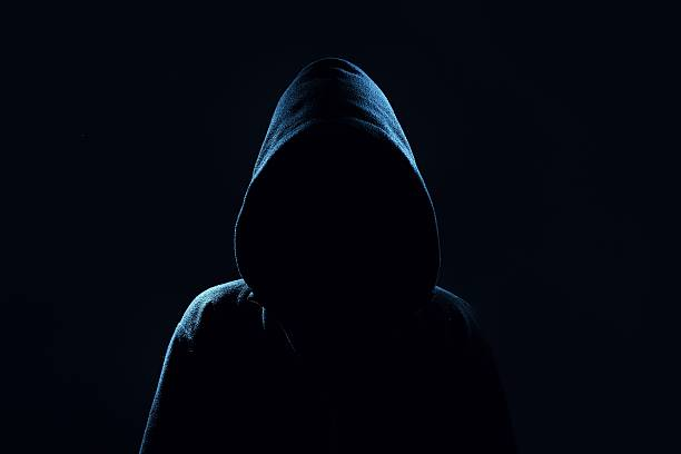 Mysterious, unknown person in the hood. Danger in darkness. stock photo