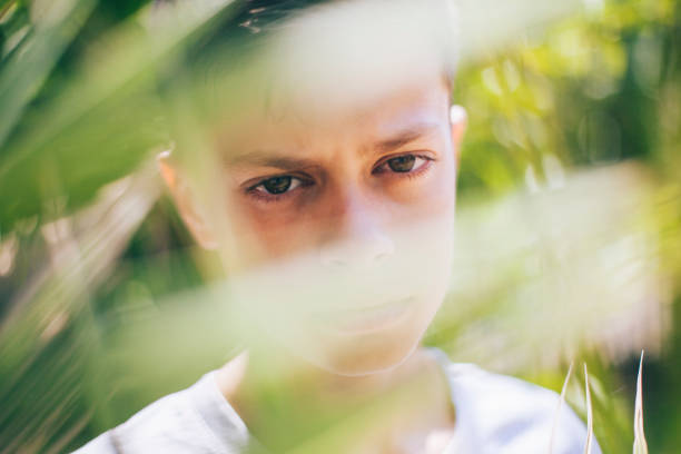 mysterious view of the boy through palm leaves - lepro stock pictures, royalty-free photos & images