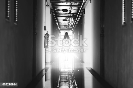 istock Mysterious Woman, Horror scene of scary ghost woman standing at corridor with light in white tone 862298914