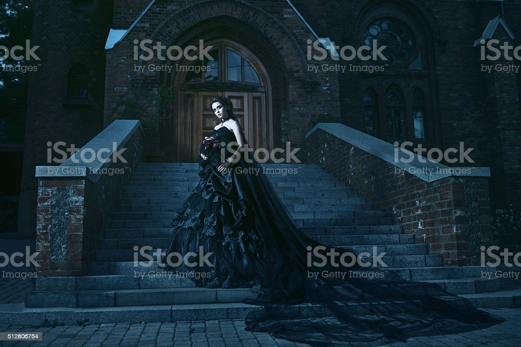 Mysterious woman in black dress near chirch stock photo