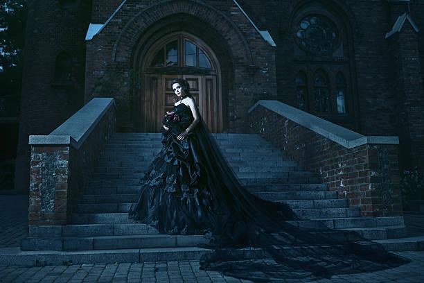 mysteriöse frau im schwarzen kleid in der nähe von kirche - gothic kleid stock-fotos und bilder