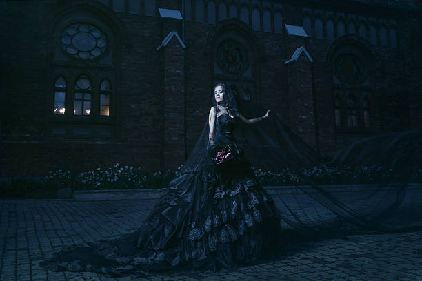 mysterious woman in black dress near chirch - gothic fashion stock photos and pictures