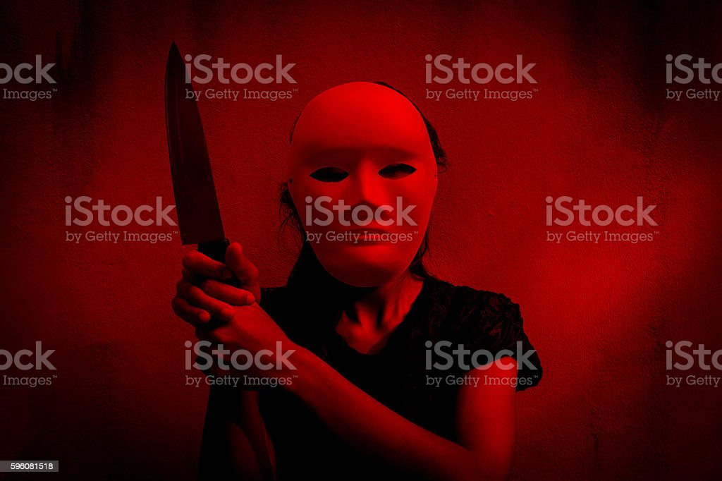 Mysterious woman in black dress wearing white mask holding knife royalty-free stock photo