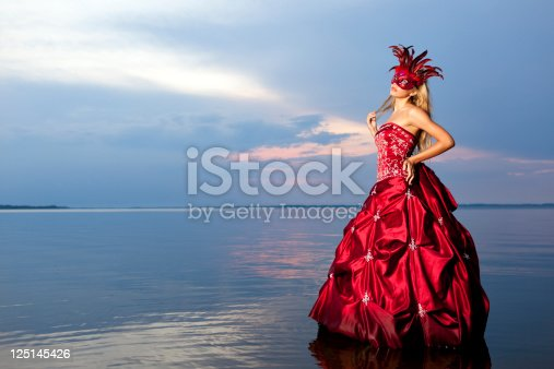 Mysterious woman in red dress with red carnival mask standing on the water in the lake and Looking away and think of something (some mosquitoes flying around)