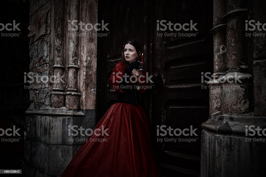Mysterious woman in red Victorian dress with a candle stock photo