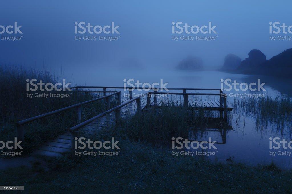 embarcadero de madera misteriosa en el lago por la noche - foto de stock