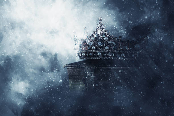mysteriousand magical image of old crown and book over gothic black background. medieval period concept. - tron zdjęcia i obrazy z banku zdjęć