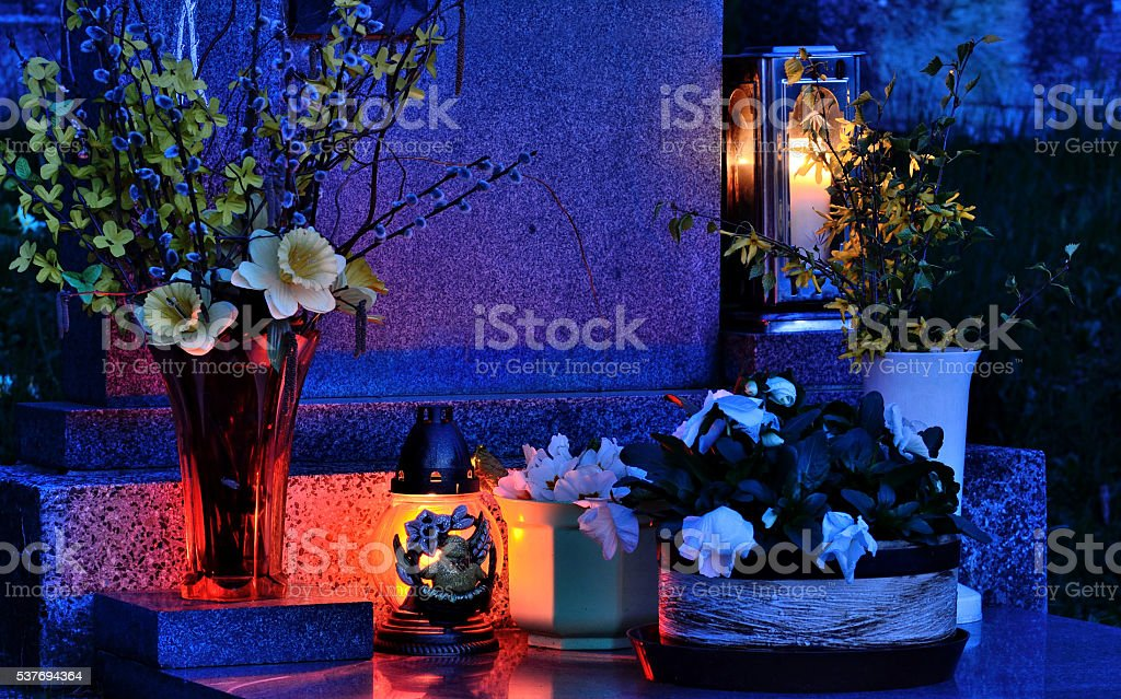 Mysteriously illuminated grave on All Souls' Day at night stock photo