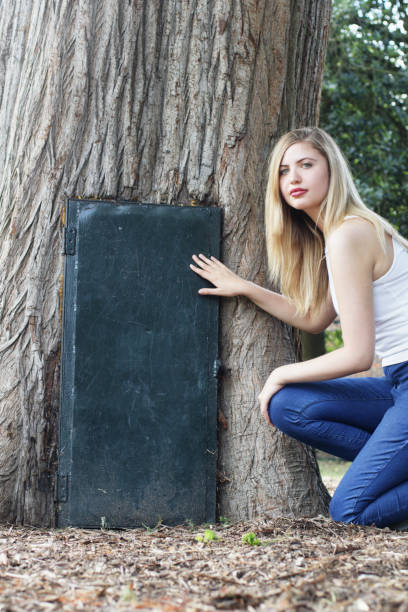 mystery door in tree with beautiful bulgarian outdoor girl - whiteway bulgarian outdoor girl stock photos and pictures