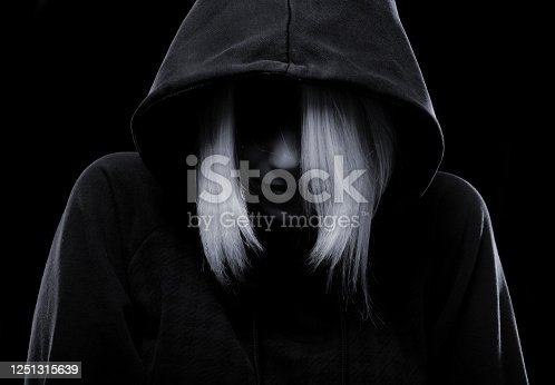 Mystery girl in sweater hiding her face under the hood isolated on black background.