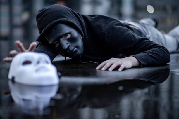 geheimnismann hoodie in schwarz maske liegen im regen versuchen, weiße maske auf nassen boden packen. major depression oder bipolaren störung. depression-konzept - zorn tod und regen stock-fotos und bilder